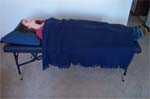 Reiki client lies on massage table with a blanket over her arms, legs and torso.