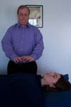 Reiki practitioner holds his hands over the client's heart chakra, channeling energy.