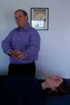 Reiki practitioner sweeps extra energy toward the client's feet.