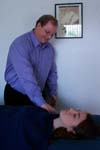 Reiki practitioner taps the client's shoulder.