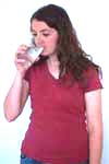 Reiki client drinks from a glass of water.
