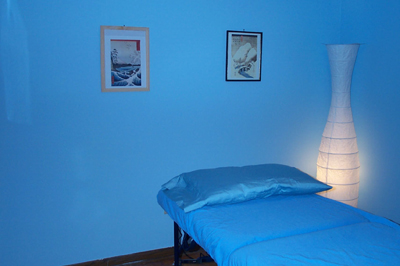 Reiki treatment and attunement room with sky blue walls, framed prints, a massage table with sky blue linens and a soft rice paper lamp.